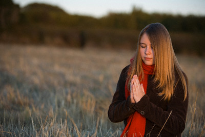 Teenage Girl Praying in a Meadow